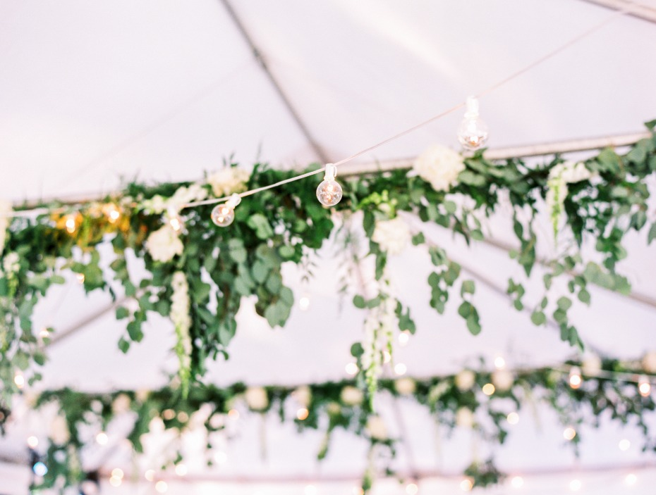 bistro lights and hanging eucalyptus brighten up the tent