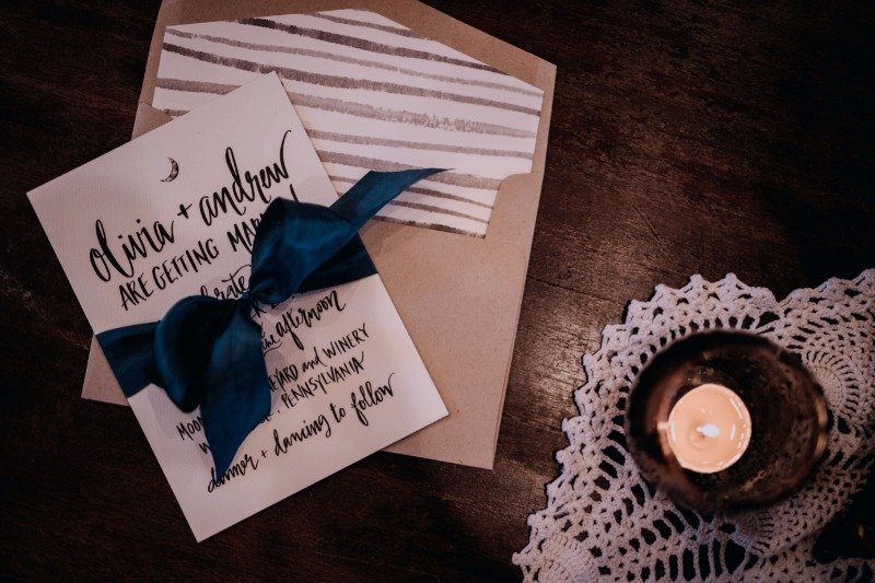 A stunning hand lettered custom invitation by Persnickety Invitation Studio with a striped envelope liner and satin ribbon.