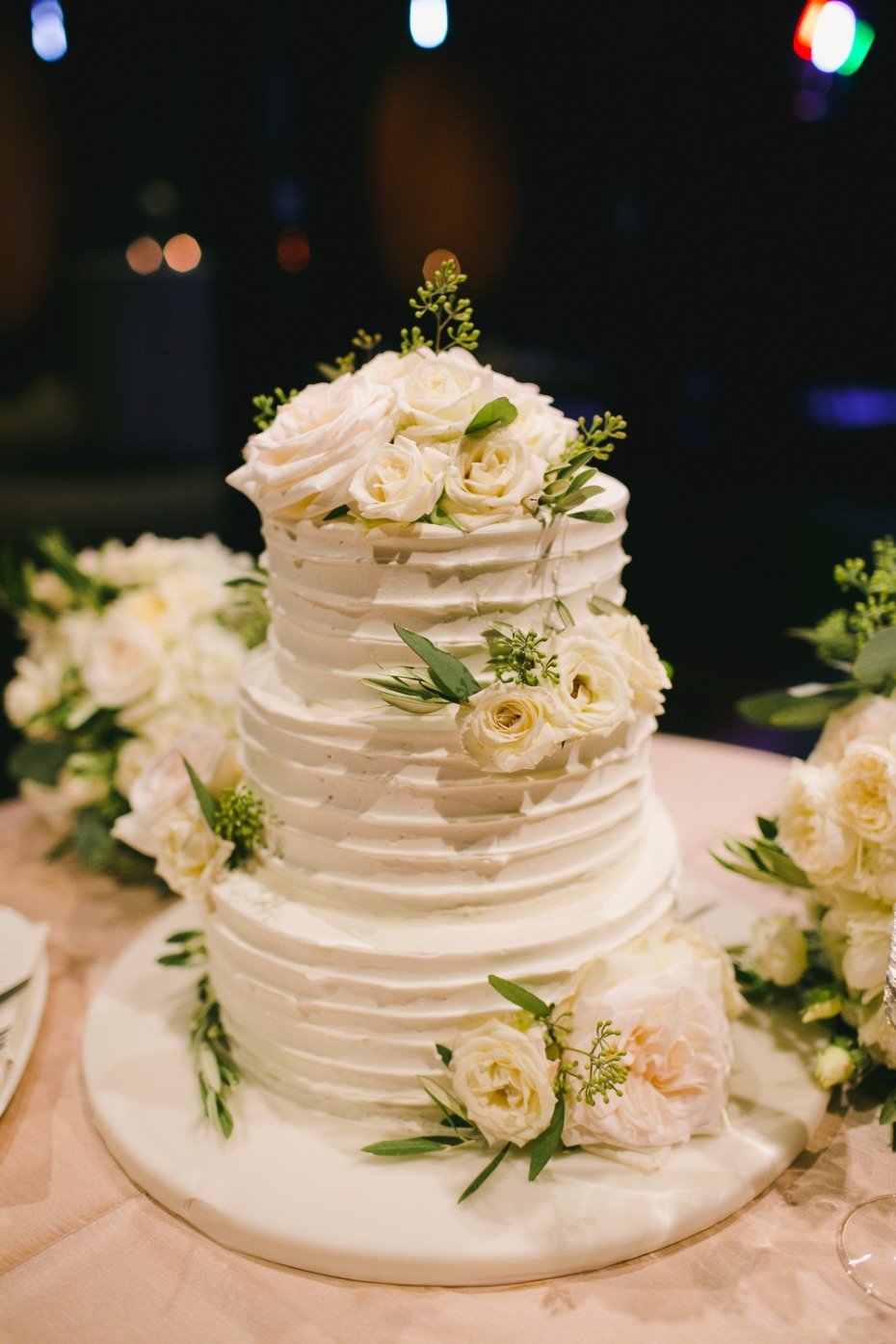 white wedding cake topped with roses and seeded eucalyptus