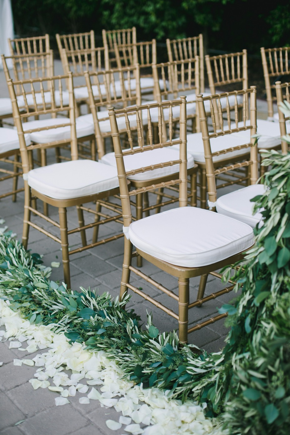 gold and white wedding chairs with greenery and white petal aisle decor