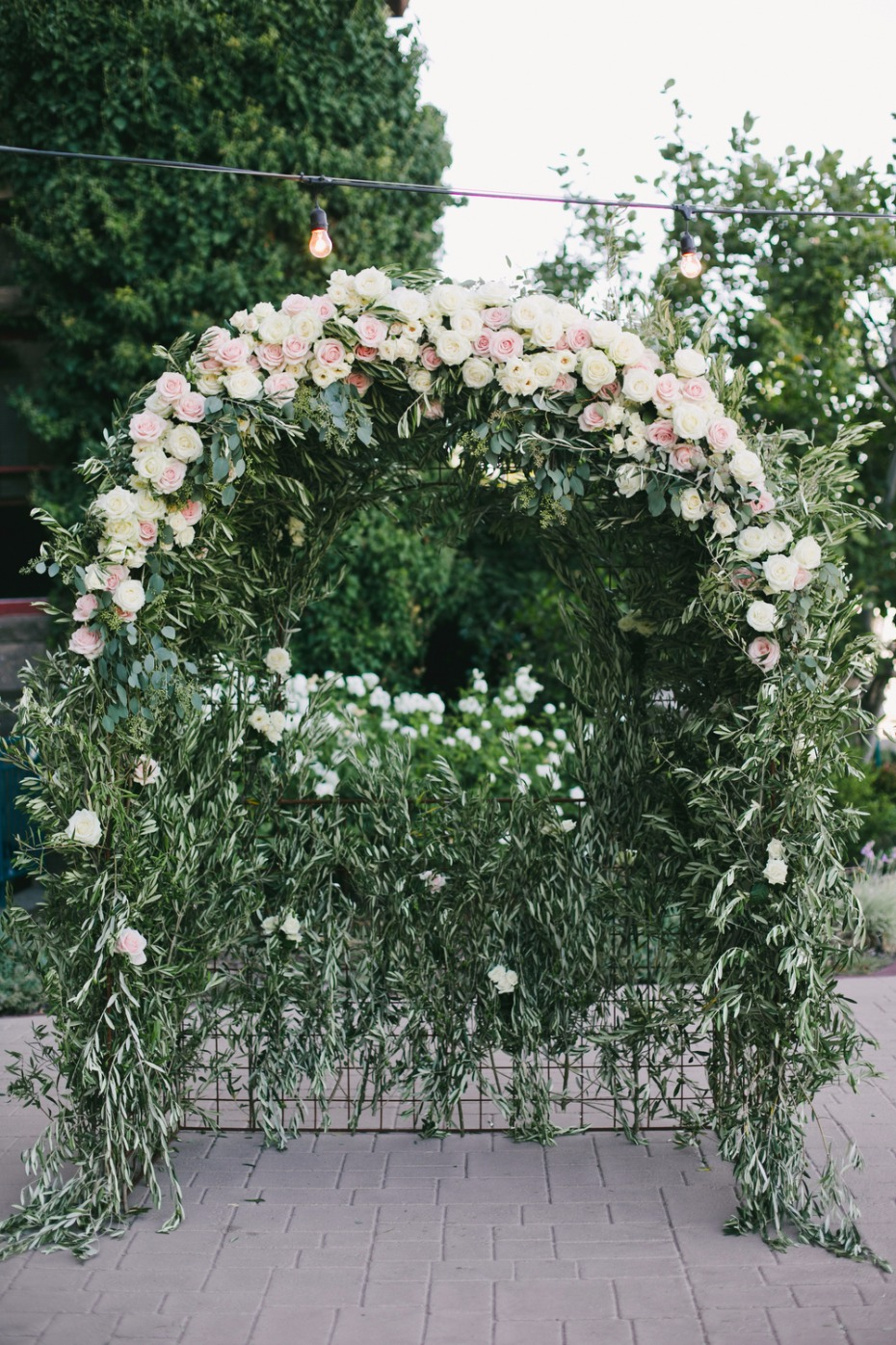 white and blush and greenery wedding arch