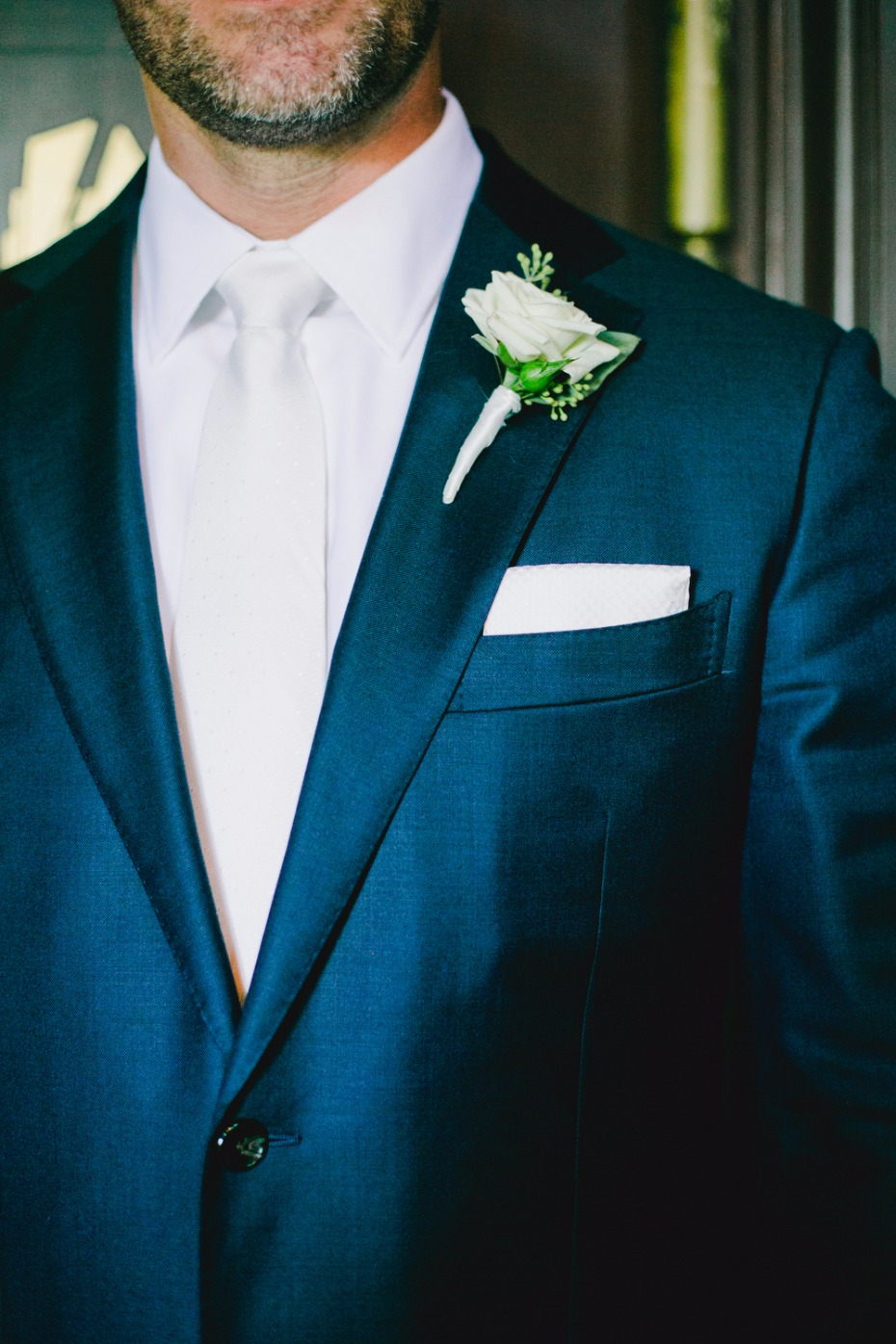 groom styled in blue suite white tie and white boutonniere