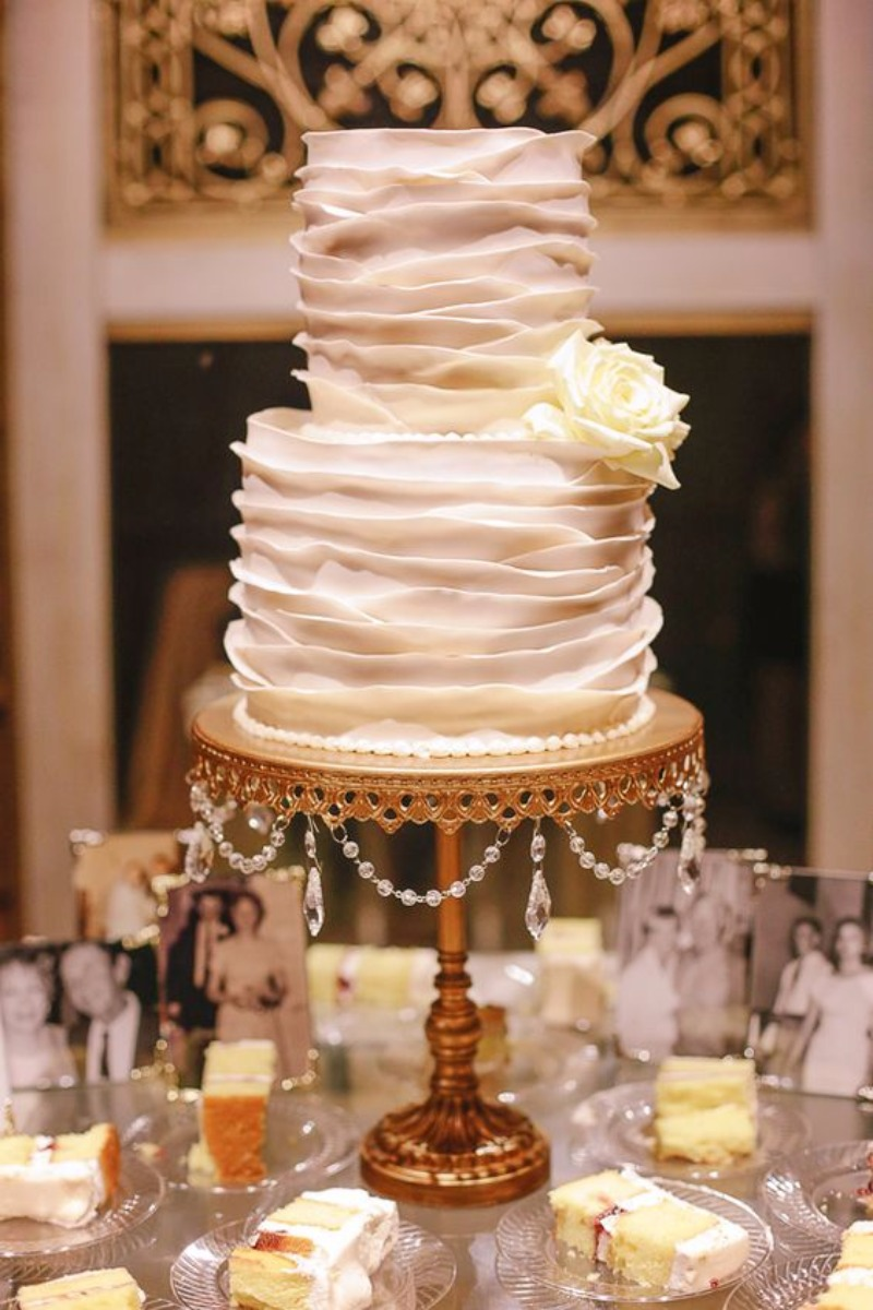Family photos are a lovely way to personalize your Wedding Cake Table! White Ruffle Frosted Tiered Wedding Cake on Opulent Treasures