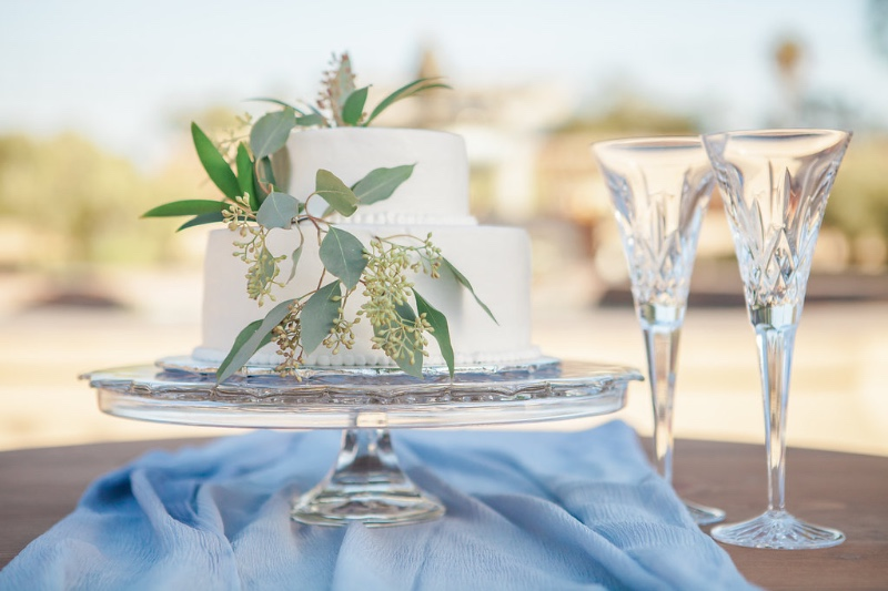 Two tier simple white wedding cake with light blue runner and greenery on a crystal cake stand. PC Linda Chaja Event Planner/Designer