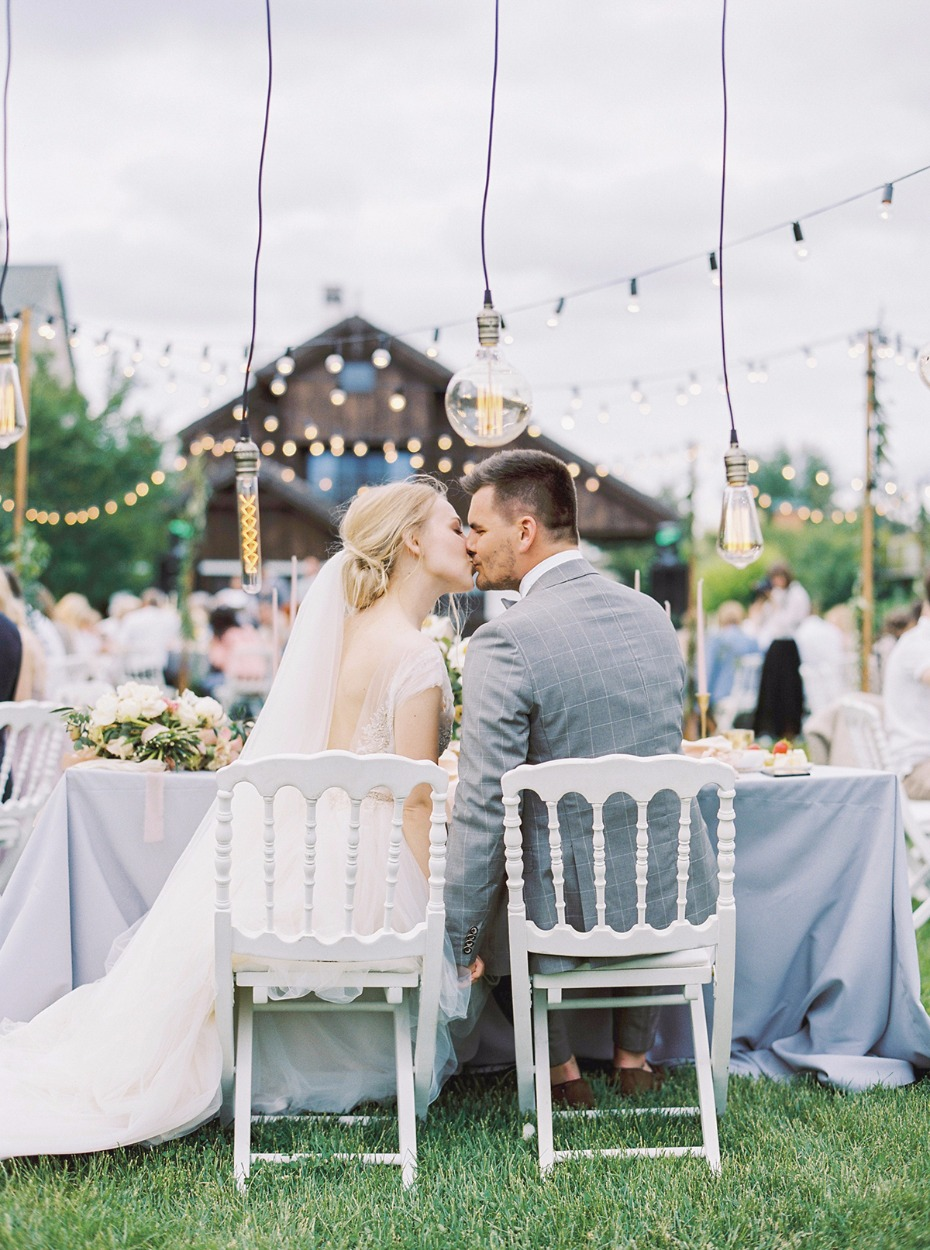 wedding kiss shared at the sweetheart table