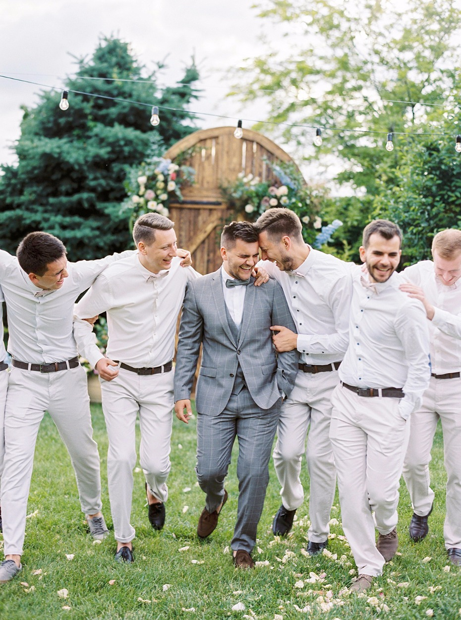 groom in light grey suit and grooms men in all white