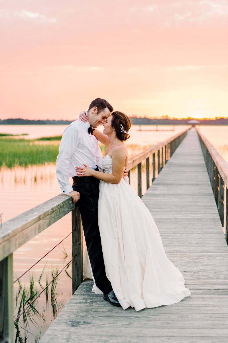 Genevieve + Pat under that cotton candy sunset | Dress: Lea-Ann Belter Diana | bridal shop: Town & Country Bridal | photographer