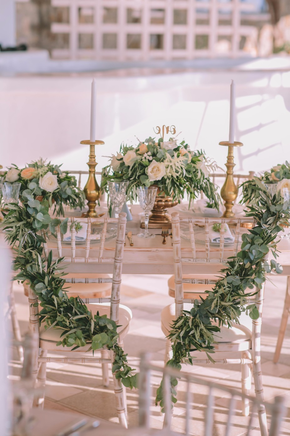 sweetheart table seats with greenery garlands