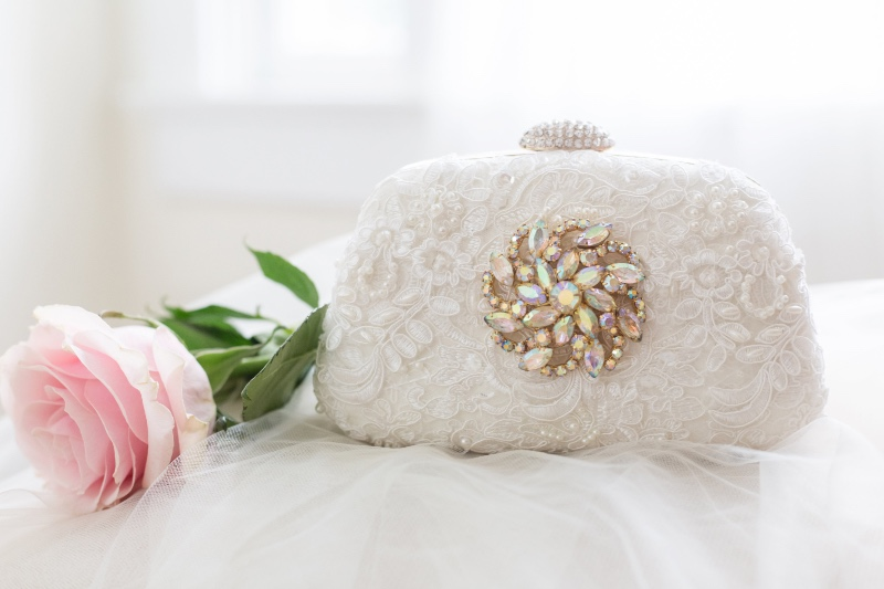 Ivory laces and a touch of a vintage jewel makes this bridal clutch the perfect keepsake.