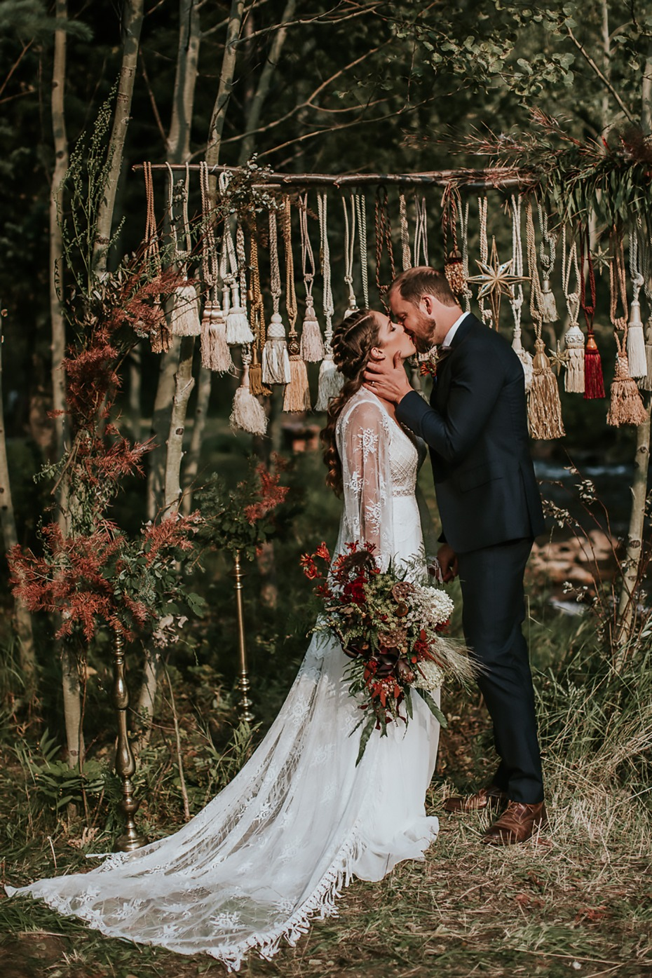 Rustic forest wedding with a vintage tassel wedding backdrop