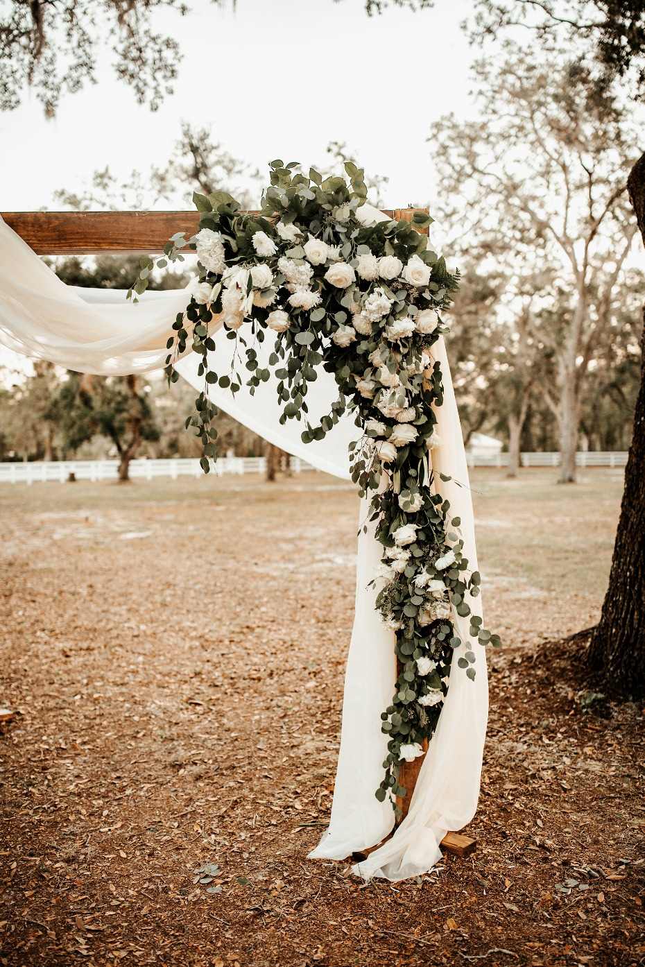 Floral wedding arch with draped fabric