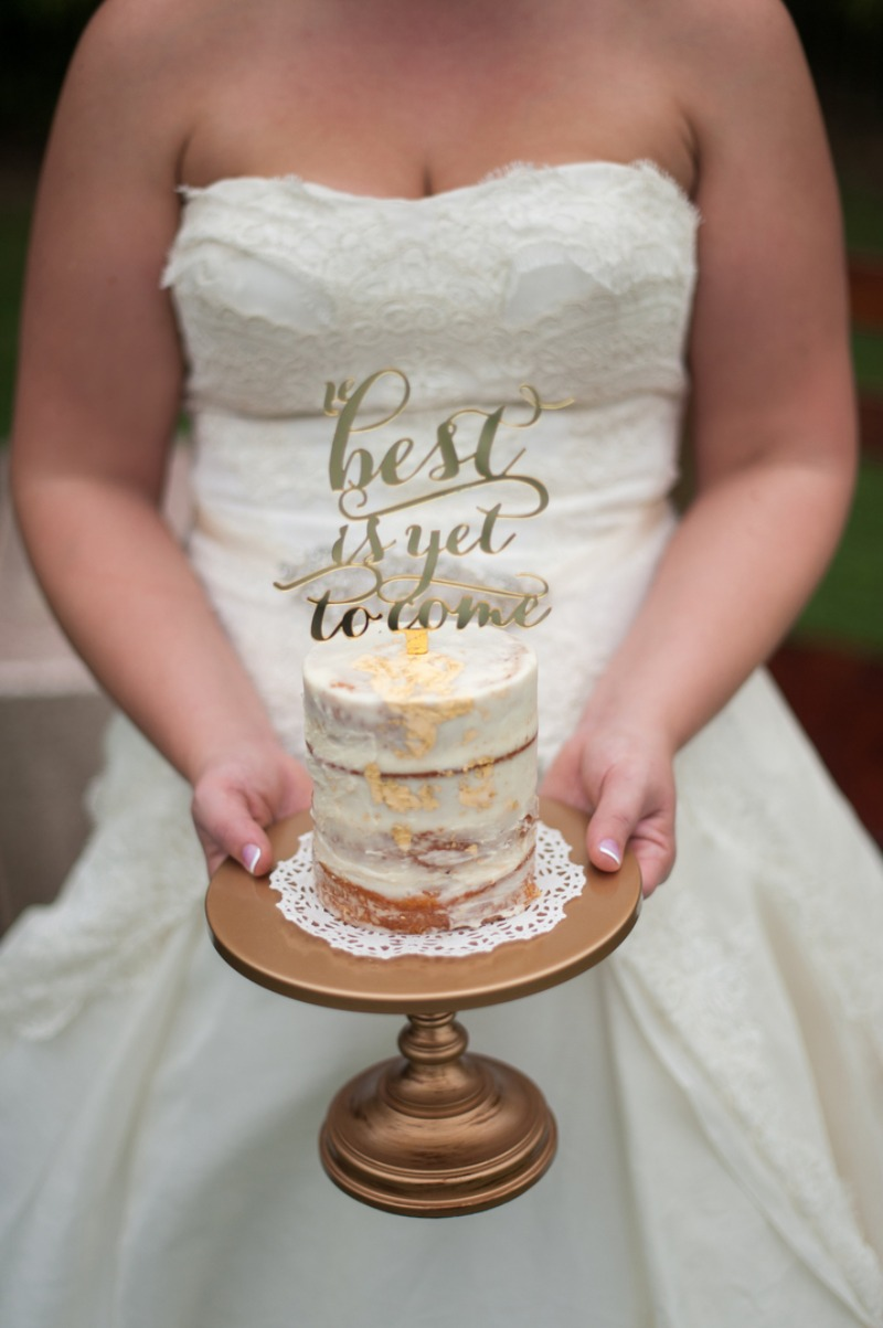 Bride holding her wedding cake on simple gold cake stand created by Opulent Treasures and Best is yet to come cake topper for Bridal