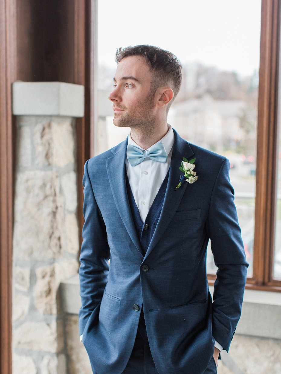 groom in navy blue suite and soft blue bow tie