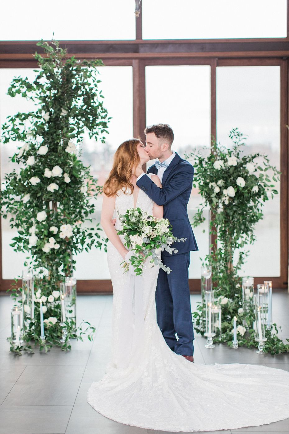 romantic wedding kiss with asymmetrical floral backdrop