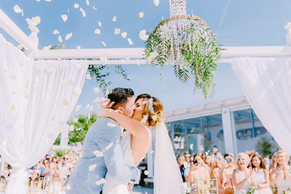wedding kiss with flower petal confetti