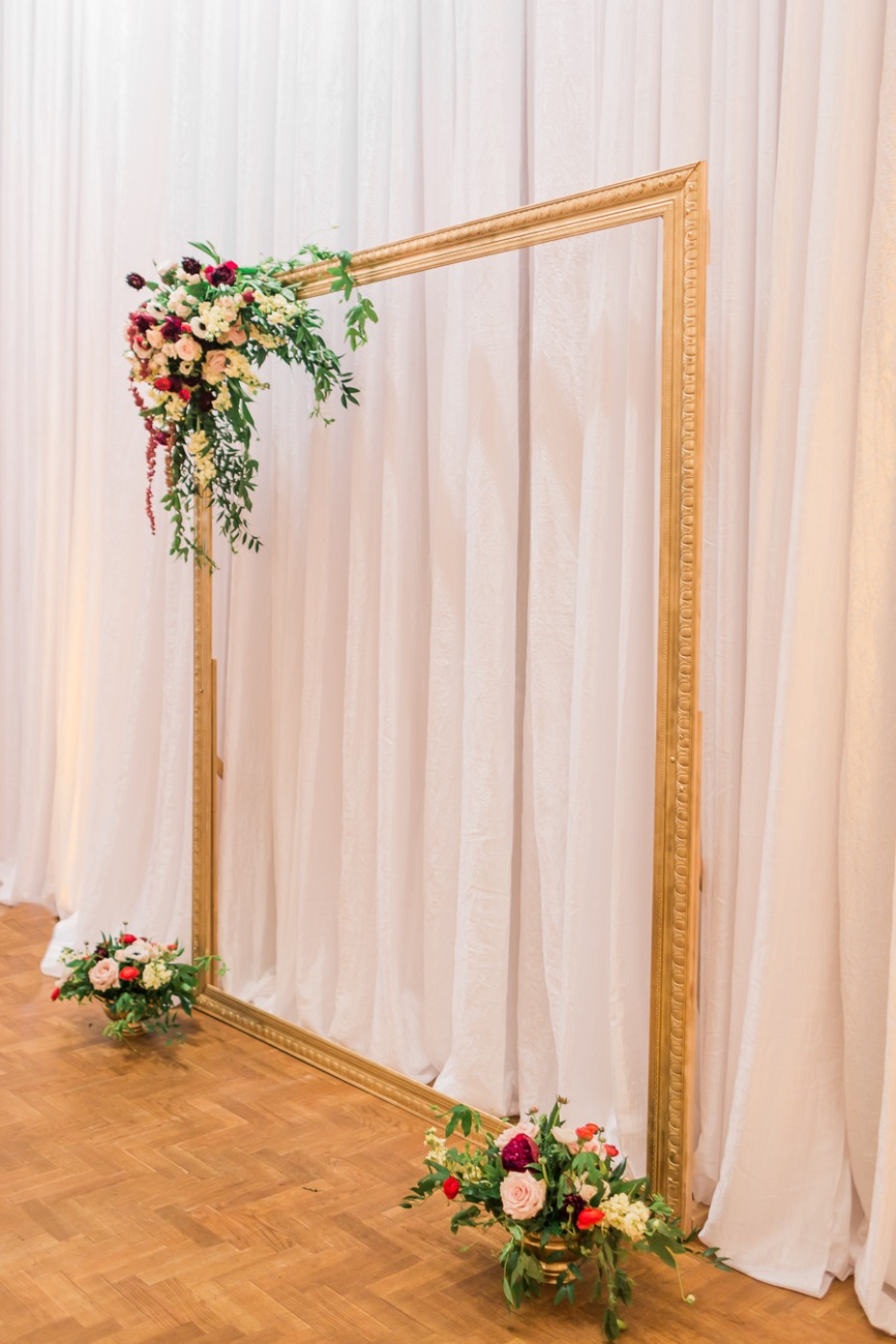 gold wedding backdrop mimics a frame for a painting