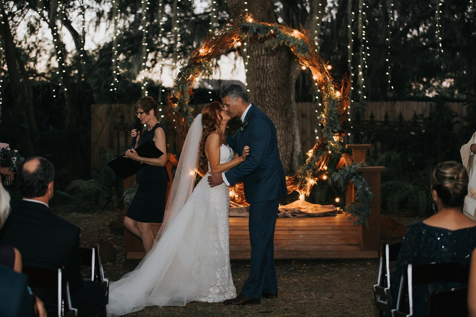 wedding kiss in front of a glowing giant wreath