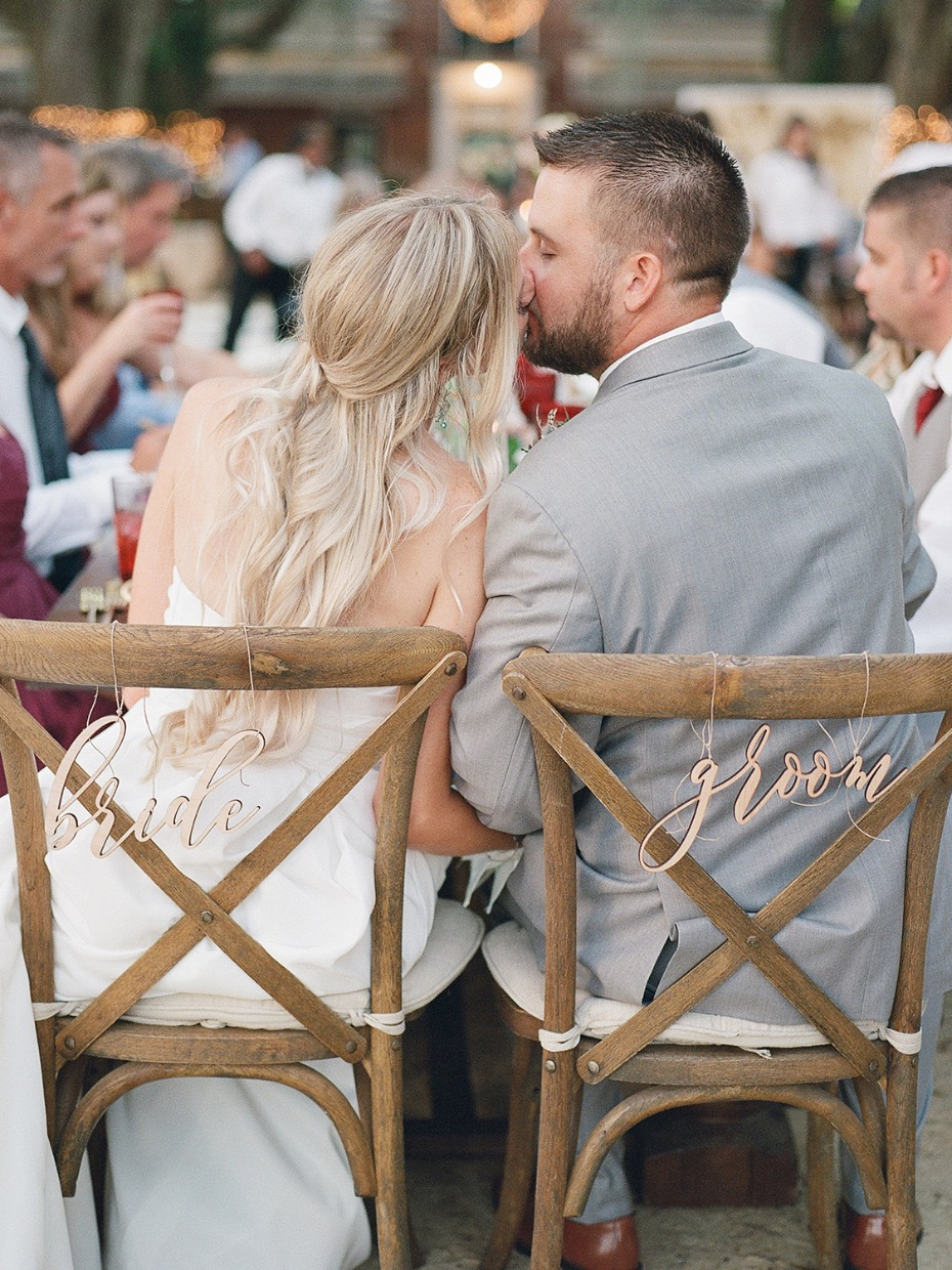 bride and groom seat signs and wedding kiss