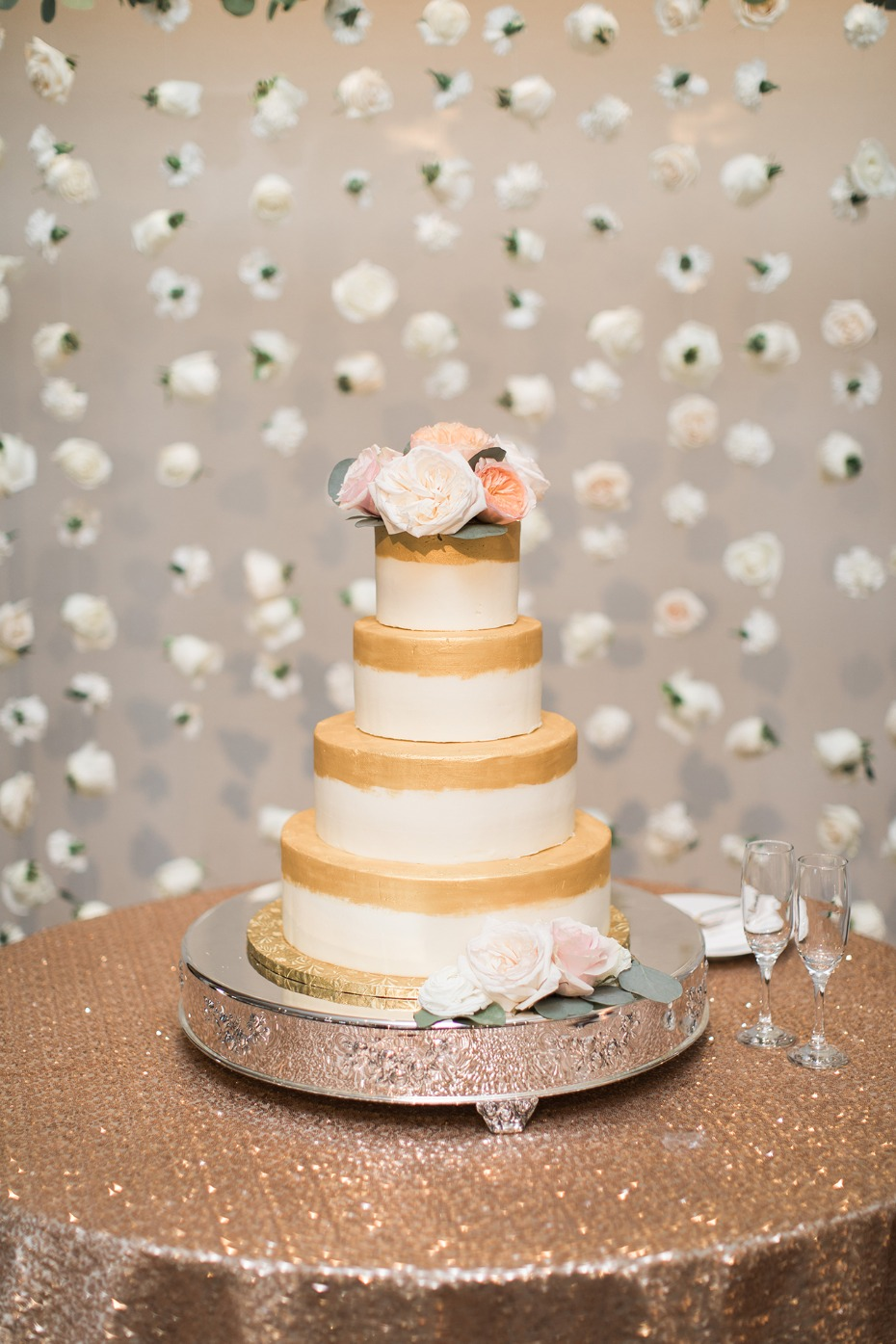 simple and sweet wedding cake with gold accents and a floating rose backdrop