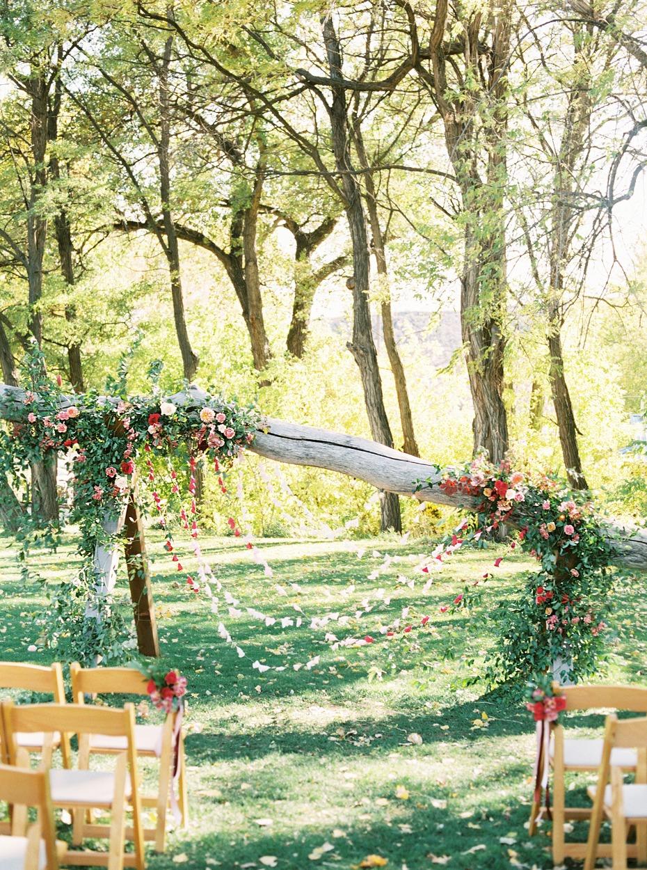 leaning bleached tree with cascading floral decor and paper backdrop