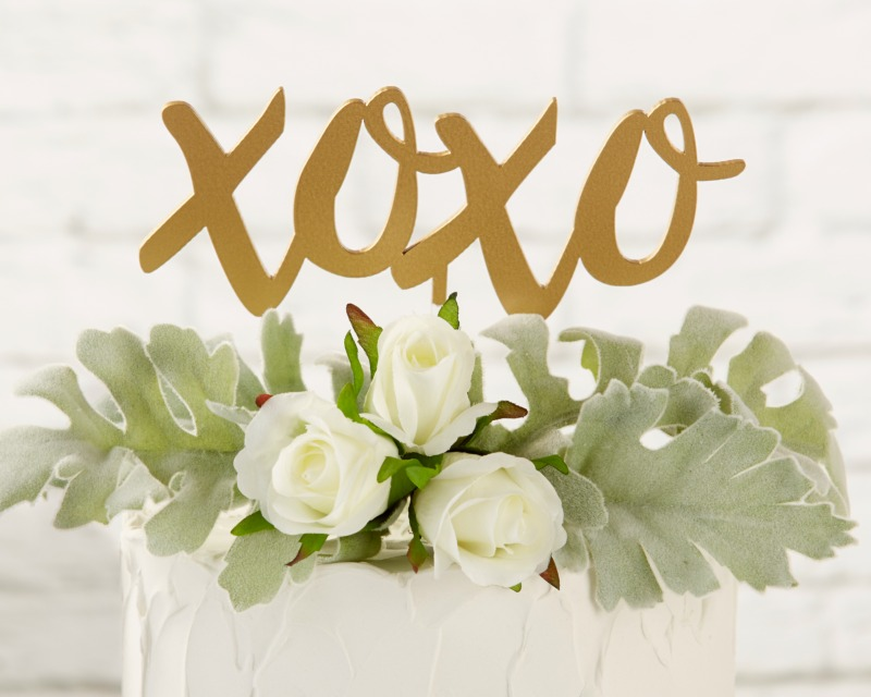 Top your wedding cake with hugs and kisses using a gold script XOXO Cake Topper!