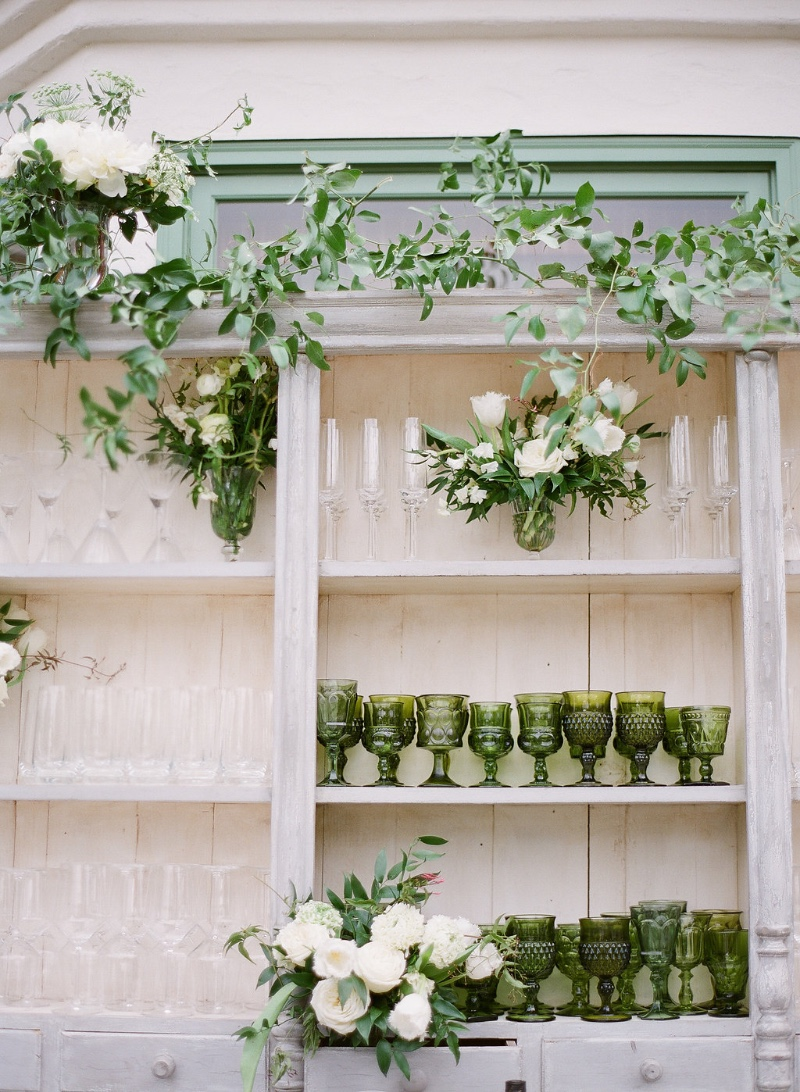 Bar back filled with vintage green glasses and green and white florals- dreamy! Planning and styling by Magnolia Event Design