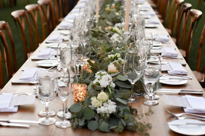 Outdoor dining with farm tables, garland and pillar candles.