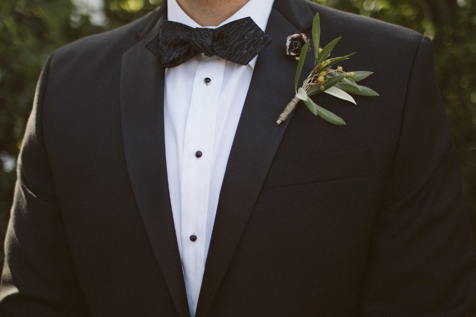 black tie groom style with a fun knife and fork patterned bow tie