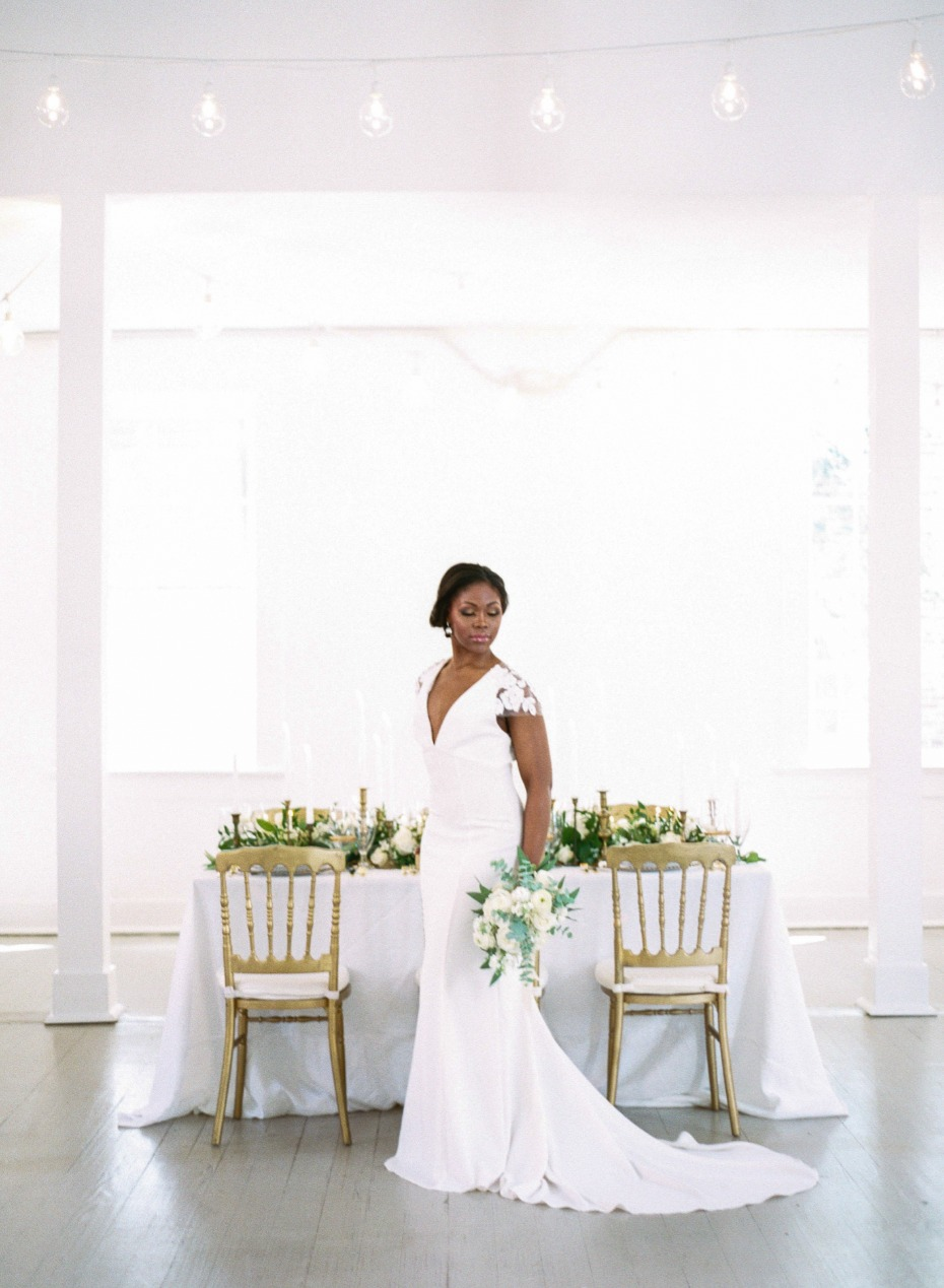 bride with her gold and white wedding decor
