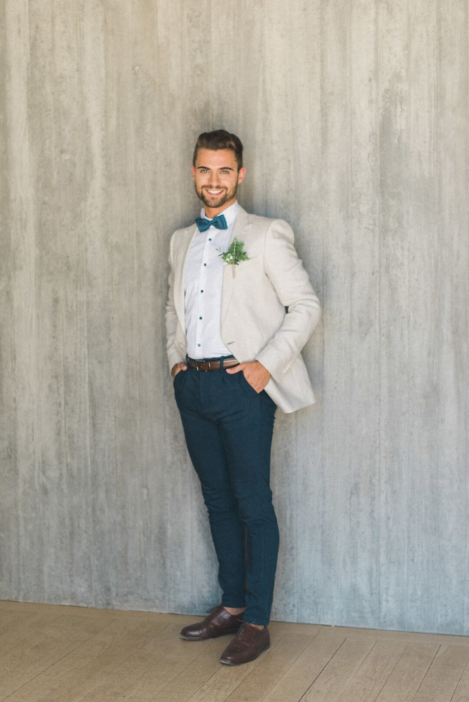 groom in cream jacket and navy pants