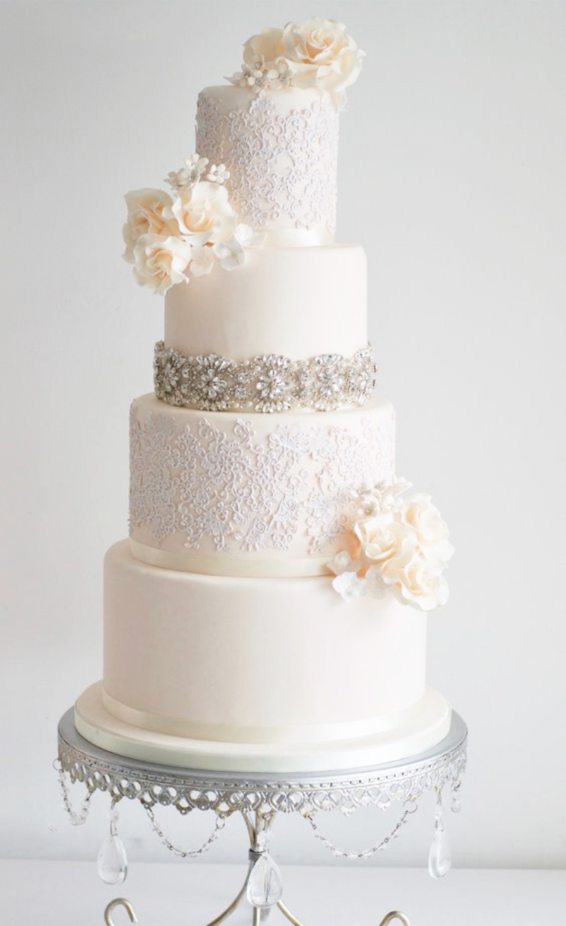Classic & Elegant. Tiered White Wedding Cake on Antique Silver Cake Stand with Chandelier Accents.
