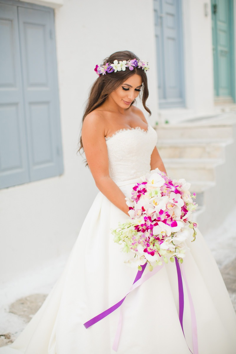 How gorgeous is this bride holding her cascading orchid bouquet? #weddingbouquet #lilyofthevalley_events #weddingingreece #greeceweddings