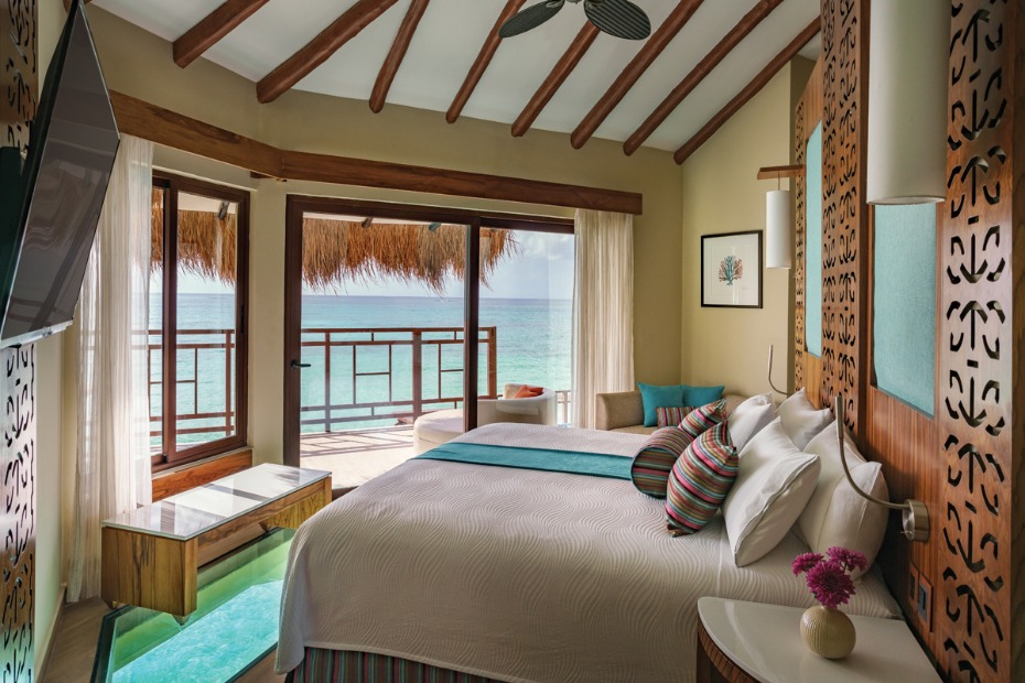 king bed  with glass floors and sweeping ocean views at the Palafitos