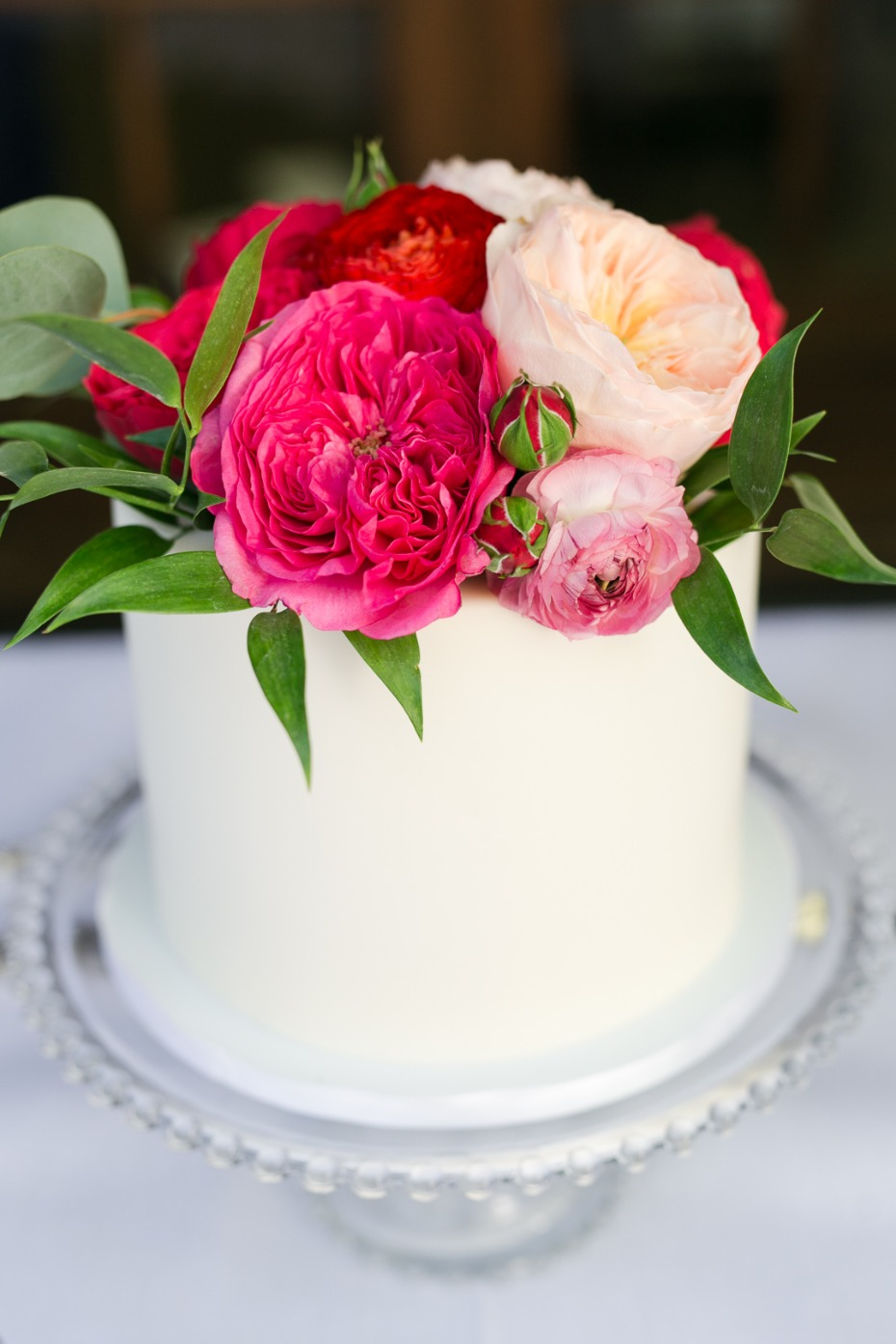 small wedding cake with hot pink and blush floral topper