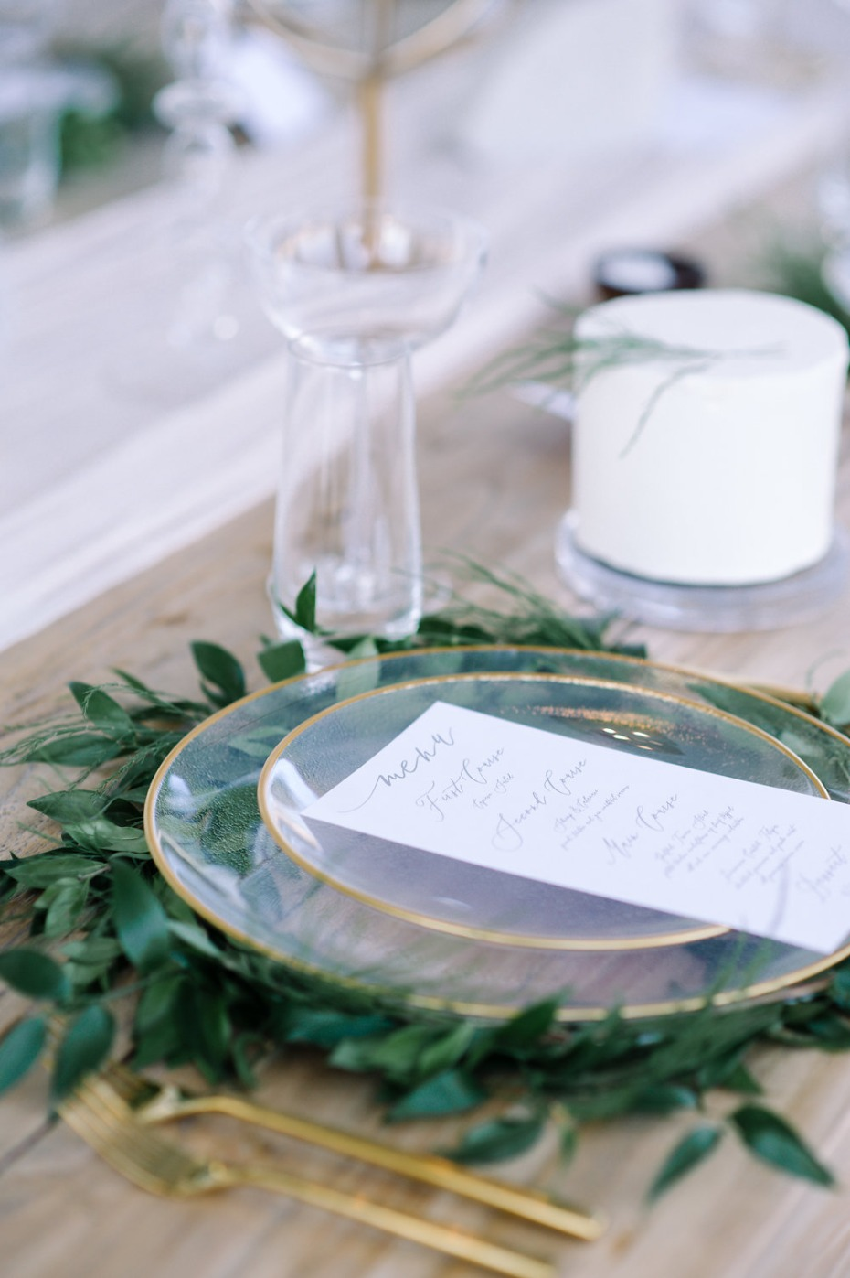 glass and gold place setting with greenery wreath charger