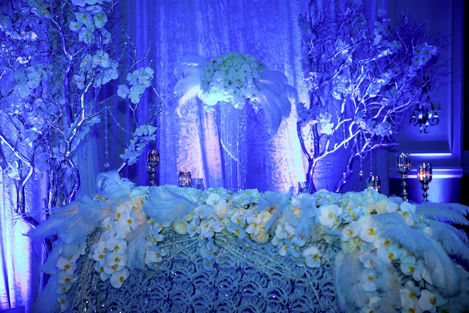 dramatic blue up lighting give this glamorous white wedding table an icy winter vibe
