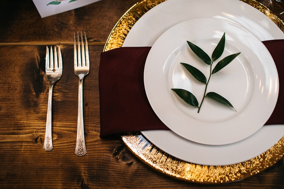 late fall wedding place setting with deep burgundy and gold accents