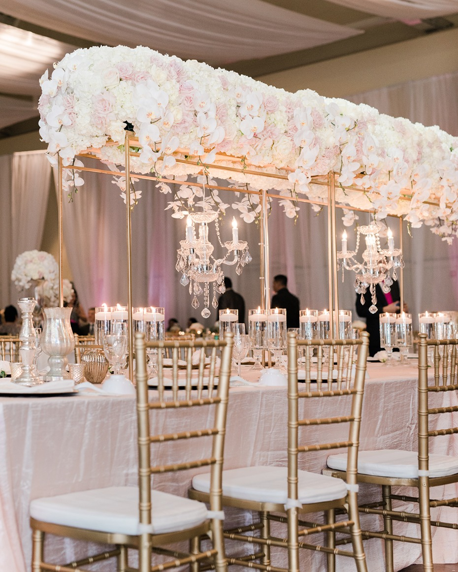 gold and white wedding decor with table halo and chandeliers