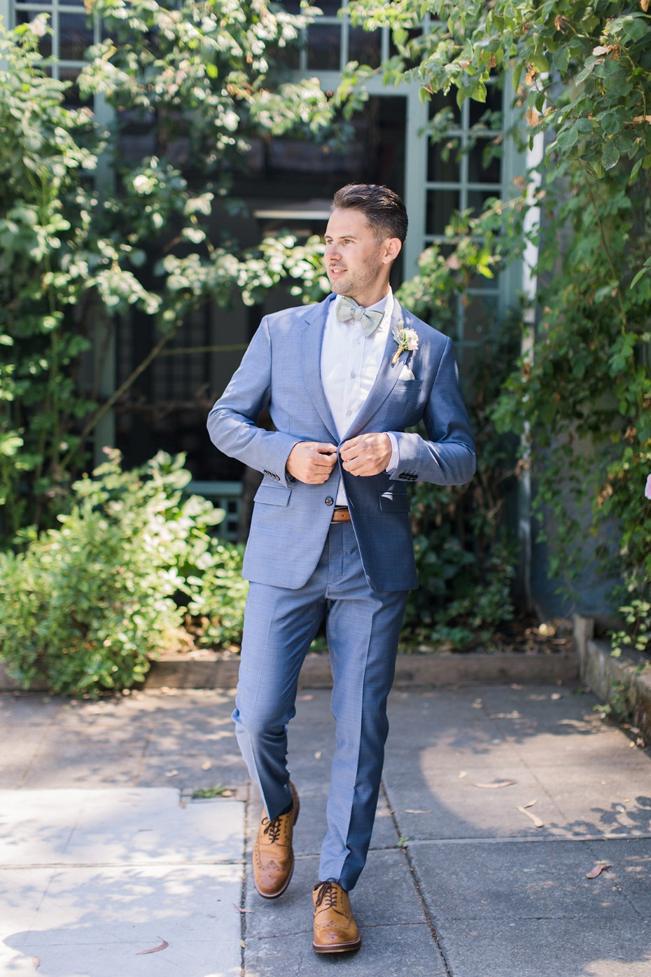 groom in blue grey suite with sage bow tie