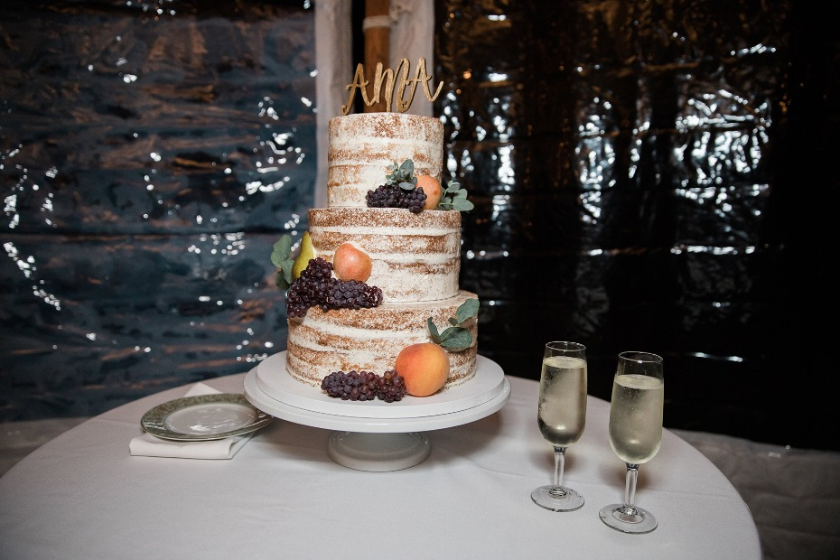 naked wedding cake topped with fresh fruit