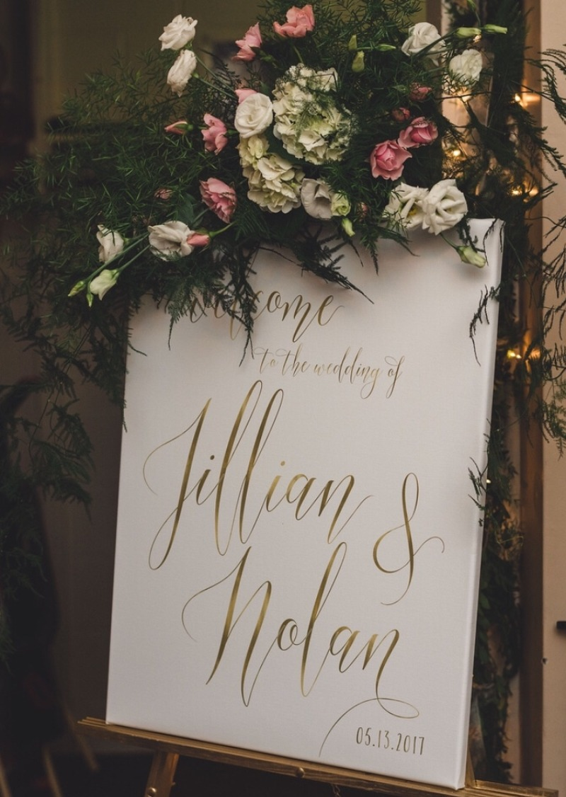 A beautiful welcome sign topped with an amazing arrangement of florals is the perfect way to welcome your guests! Miss Design Berry