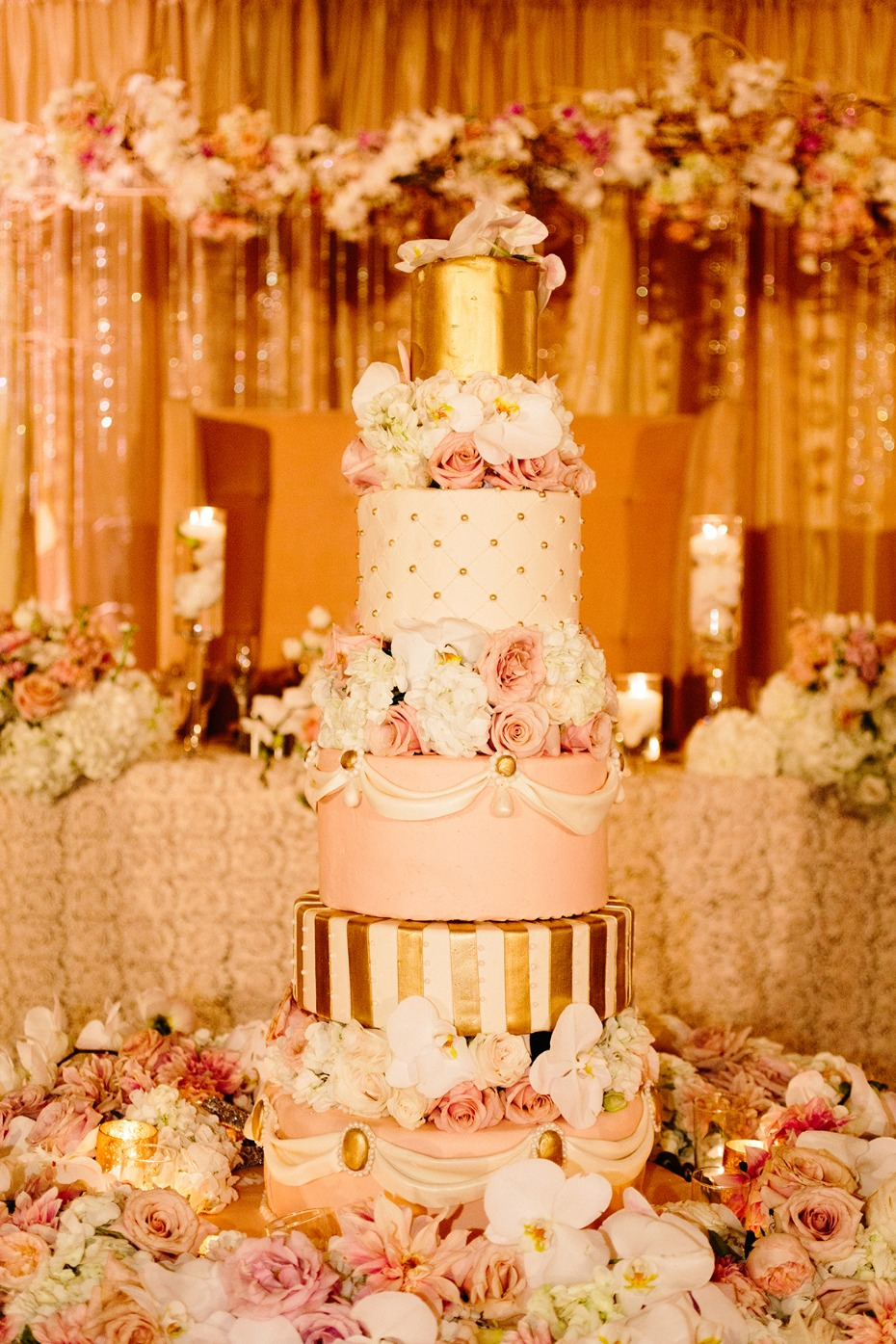 Gold white and blush wedding cake and flowers