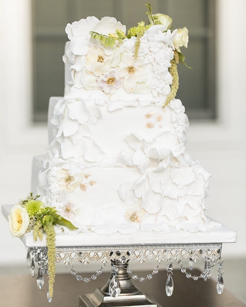 Pretty petal covered wedding cake on an antique silver square chandelier cake stand created for your wedding day by Opulent Treasures