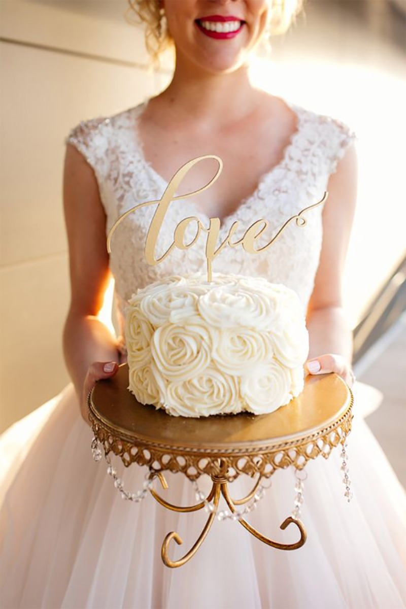 Love this Bride holding her wedding cake on an antique gold chandelier cake stand topped with love cake topper!