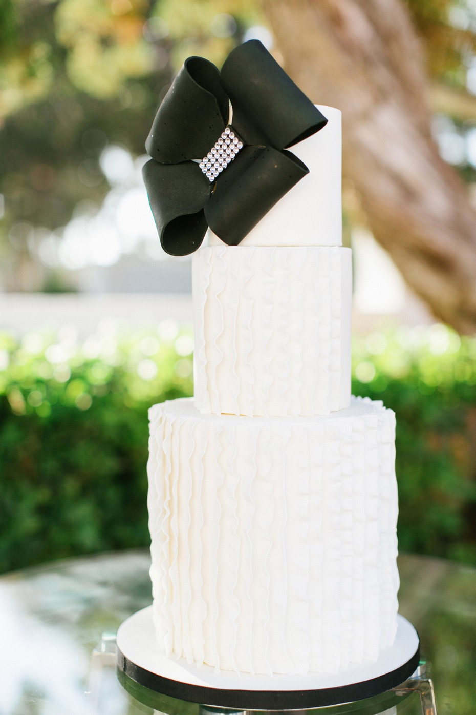 Modern white ruffle cake with black bow