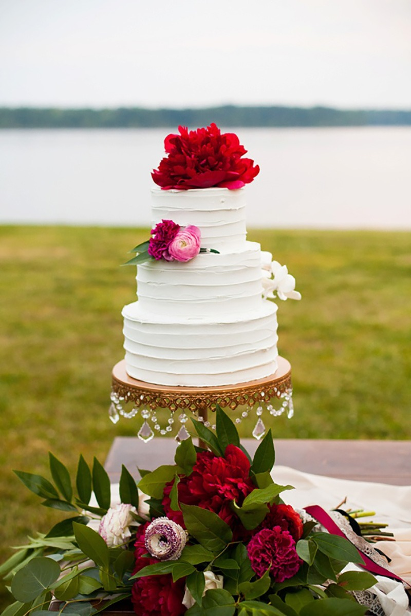 Rich ruby jeweled-toned wedding cake on an Opulent Treasures antique gold chandelier cake stand.
