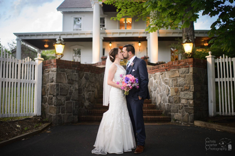 A kiss in front of FEAST at Round Hill, Hudson Valley wedding venue. Photo by Chris Carter Photography.