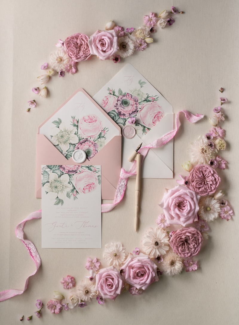 Wedding invitations with pastel pink flowers and silk ribbon