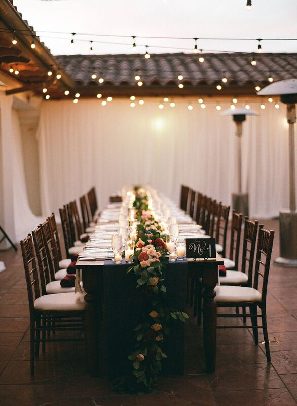 Table setting dripping with flowers. Guest names were written on tiles and calligraphy table numbers were perched on the end of the