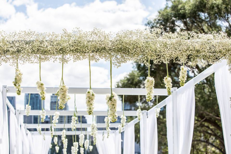 Hanging Fresh Florals lining the wedding arbour aisle.